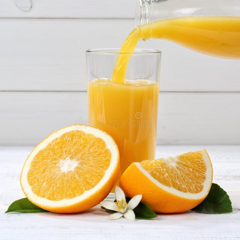 O derramamento do suco de laranja derrama frutos quadrados do fruto das laranjas imagem de stock