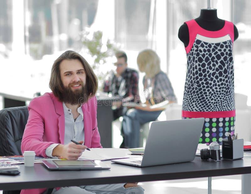 O desenhador de moda usa uma tabuleta gráfica que senta-se em uma mesa no estúdio fotografia de stock royalty free