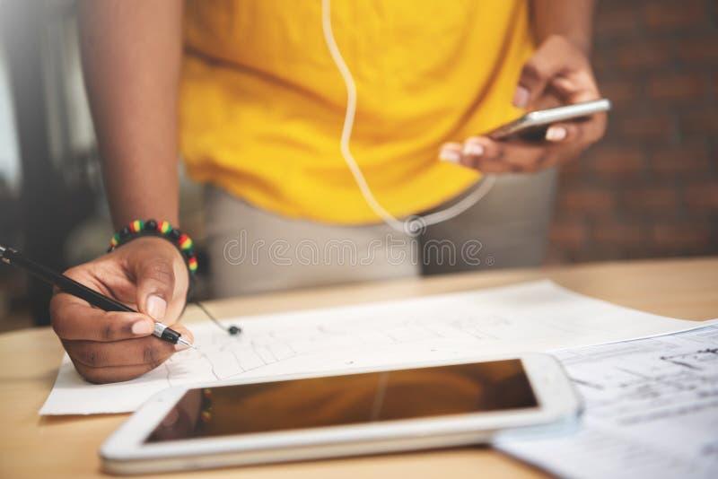 O desenhista africano na camisa amarela está trabalhando com drawi de esboço fotos de stock