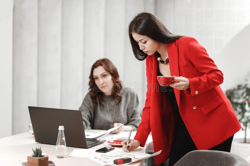 O desenhista de duas jovens mulheres est? trabalhando no projeto de design do interior na mesa com port?til e da documenta??o no imagens de stock