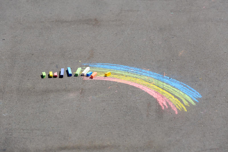 O desenho da criança do arco-íris e dos gizes em uma rua foto de stock