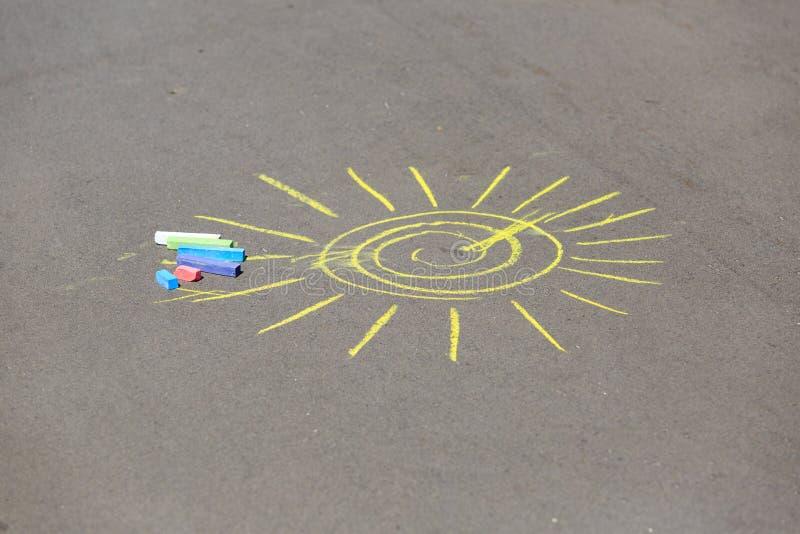 O desenho da criança do sol e dos gizes em uma rua imagens de stock royalty free