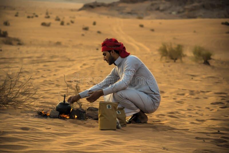 O deserto Jordânia de Wadi Rum 17-9-2017 um homem beduíno, faz um fogo no meio do deserto do rum do barranco entre pedras, põe um imagens de stock