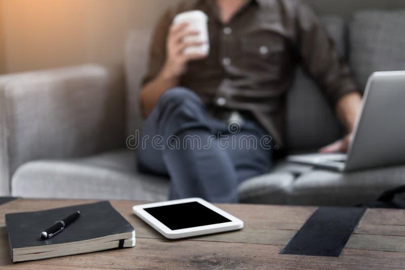 O desktop de trabalho do negócio com homem de negócios funciona no sofá em h foto de stock