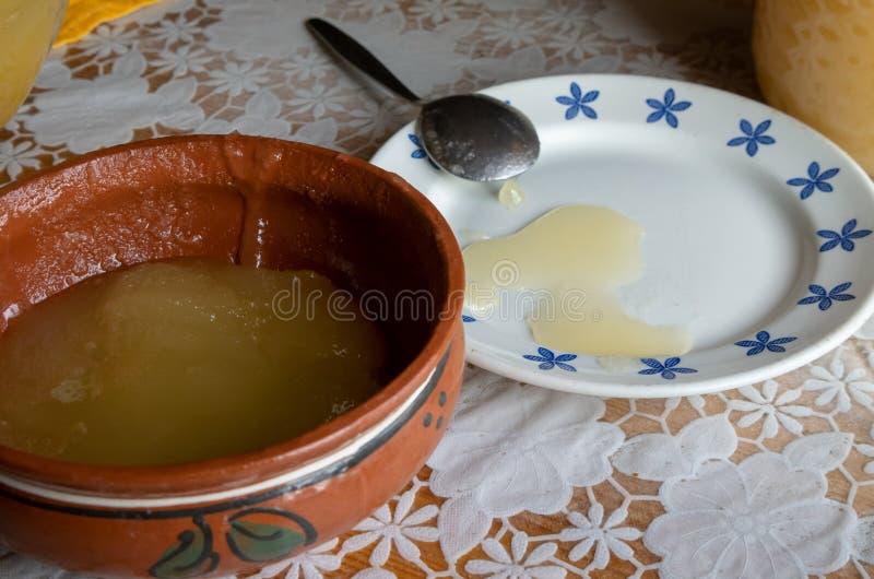 O deslocamento do mel de um recipiente maior em uma bacia fotos de stock royalty free