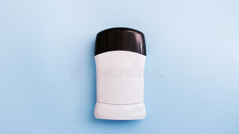 O desodorizante ou o antiperspirante dos homens isolado no fundo azul com espaço da cópia Conceito do cuidado do corpo imagens de stock