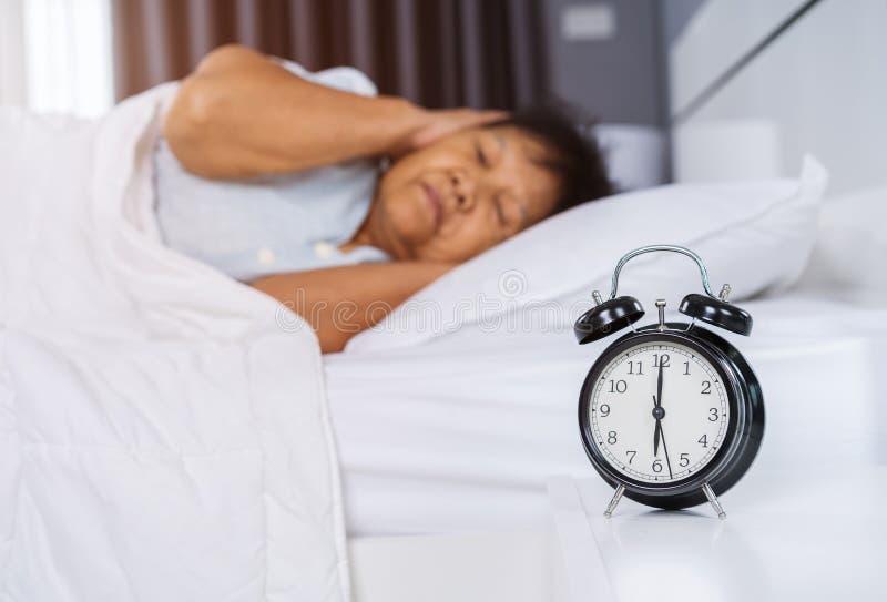 O despertador acorda na manhã e no fim superior da mulher suas orelhas foto de stock