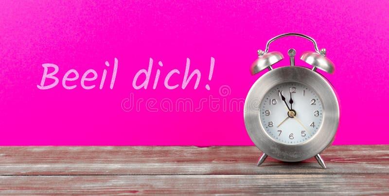 o despertador com fundo cor-de-rosa com dich alemão do beeil do texto, no inglês apressa-se acima imagem de stock royalty free