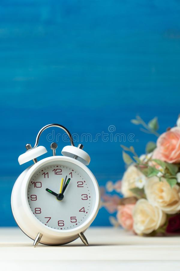 O despertador e as flores brancos rosa e rosa vermelha na tabela de madeira e fundo azul com espaço da cópia para adicionam o tex fotografia de stock royalty free