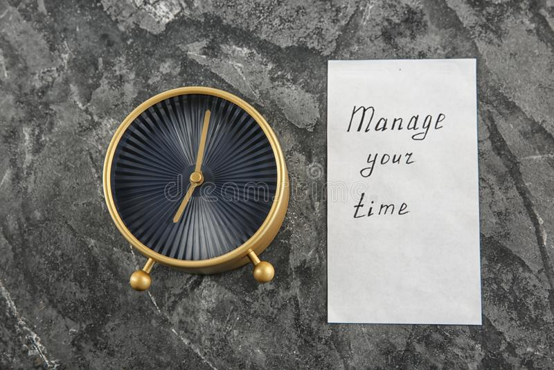 """O despertador e a folha de papel com frase \ """"controlam seu tempo \"""" no fundo textured cinzento foto de stock royalty free"""