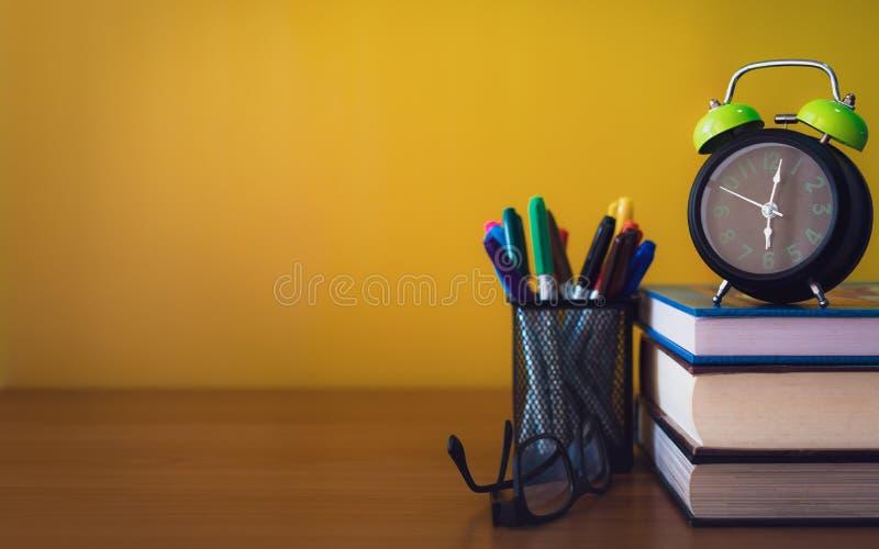 O despertador, os espetáculos, as penas da cor e a pilha de livros estão tabela de madeira no fundo amarelo isolado imagem de stock royalty free