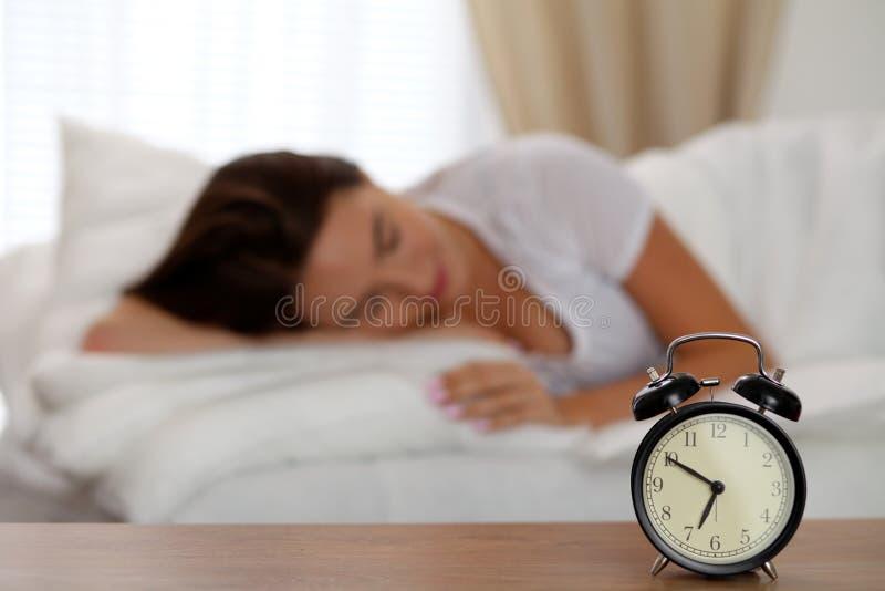 O despertador que está na tabela de cabeceira tem já soou o amanhecer para acordar a mulher na cama que dorme no fundo imagens de stock