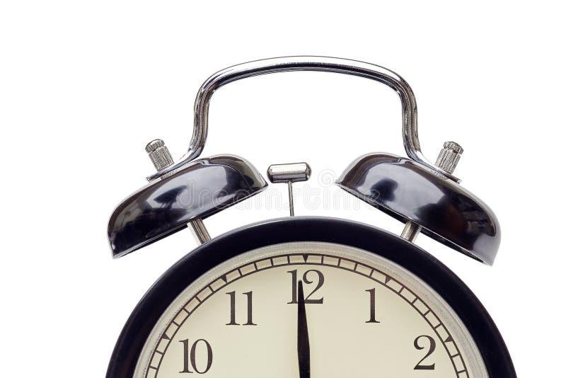 O despertador simples clássico preto com o seletor bege que mostra a mão minúscula quase em doze, em tempo idos quase ou veio, is foto de stock