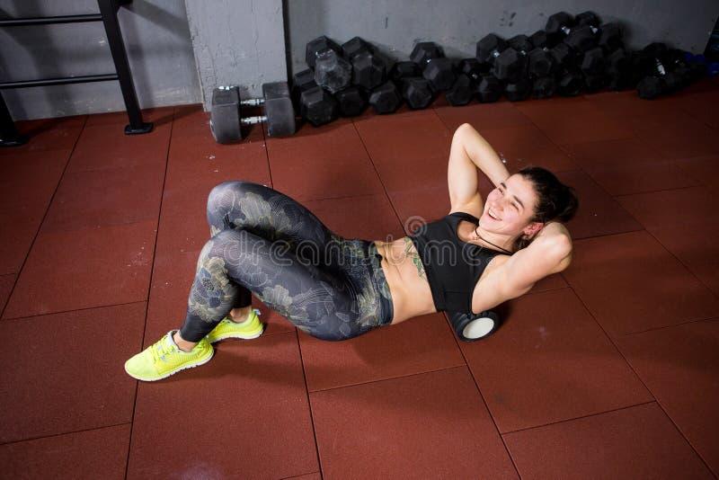 O desportista caucasiano novo bonito da mulher usa um massager do rolo da espuma para o abrandamento, esticando os músculos e a d foto de stock