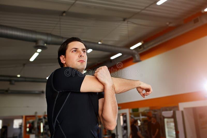 O desportista novo que está interno e que estica o tríceps antes do gym malha fotografia de stock