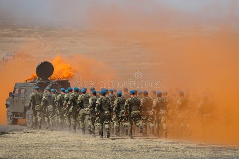 O destacamento de paramilitares do russo corre para um carro blindado através do campo no fumo alaranjado protetor fotografia de stock