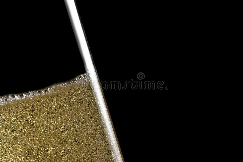 O detalhe alto de uma flauta inclinou do champanhe com bolhas douradas fotografia de stock