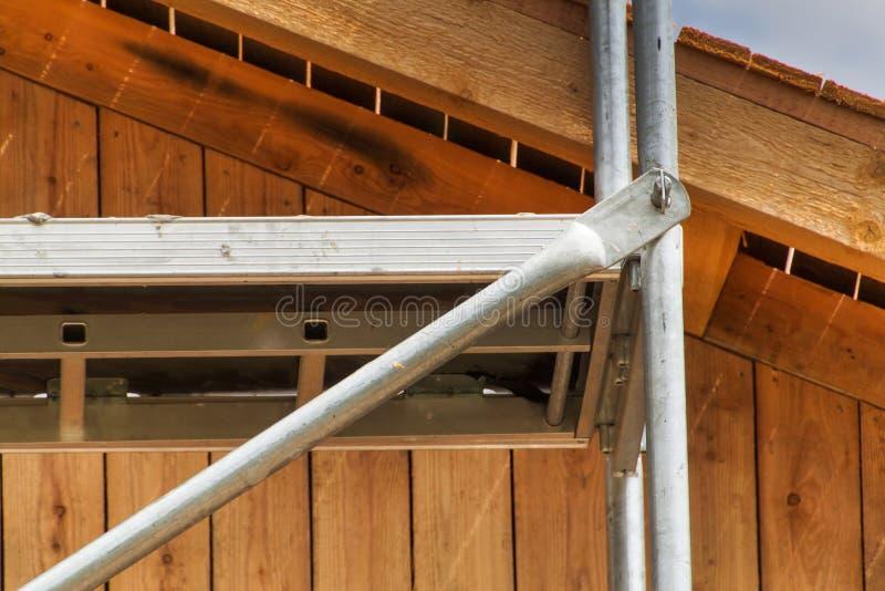 O detalhe de andaime articula na construção de uma casa da família Trabalhe em um terreno de construção de uma casa ecológica fotos de stock