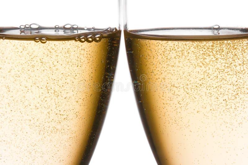 O detalhe de elogios com dois vidros do champanhe com ouro borbulha imagem de stock