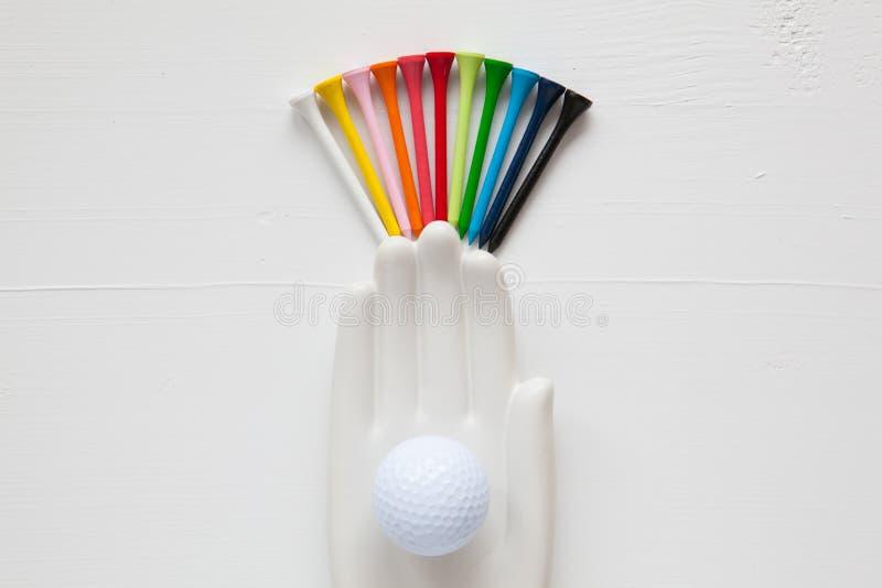 O detalhe de mão cerâmica com bolas de golfe e os T no branco cortejam foto de stock royalty free