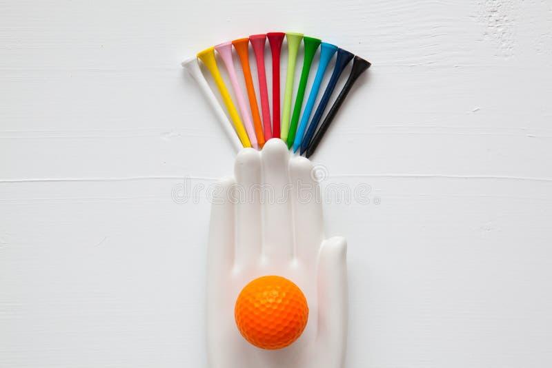 O detalhe de mão cerâmica com bolas de golfe e os T no branco cortejam imagem de stock royalty free