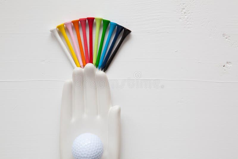 O detalhe de mão cerâmica com bolas de golfe e os T no branco cortejam fotos de stock