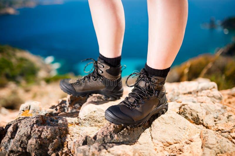 O detalhe de pés das mulheres em trekking de couro marrom calça a posição na rocha fotos de stock