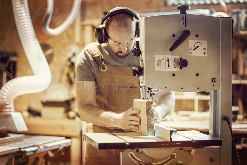 O detalhe de um carpinteiro no trabalho que corta uma prancha com uma faixa considerou em sua oficina foto de stock royalty free