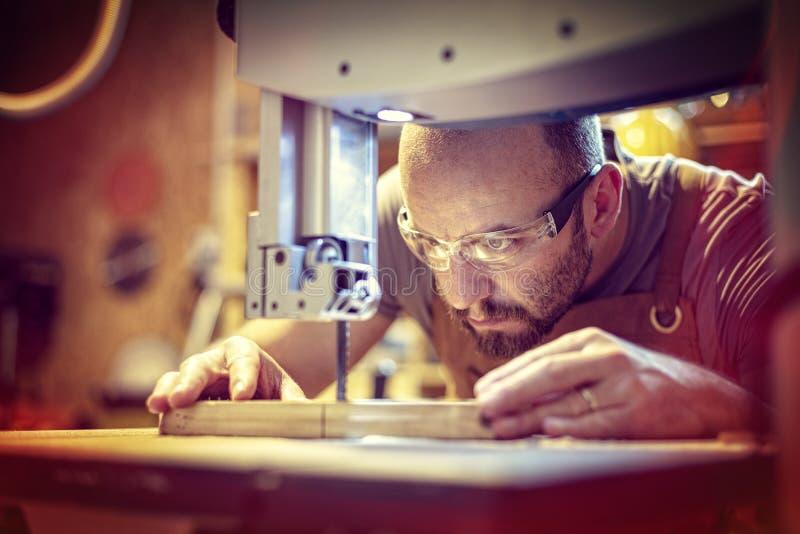 O detalhe de um carpinteiro no trabalho que corta uma prancha com uma faixa considerou em sua oficina fotos de stock royalty free