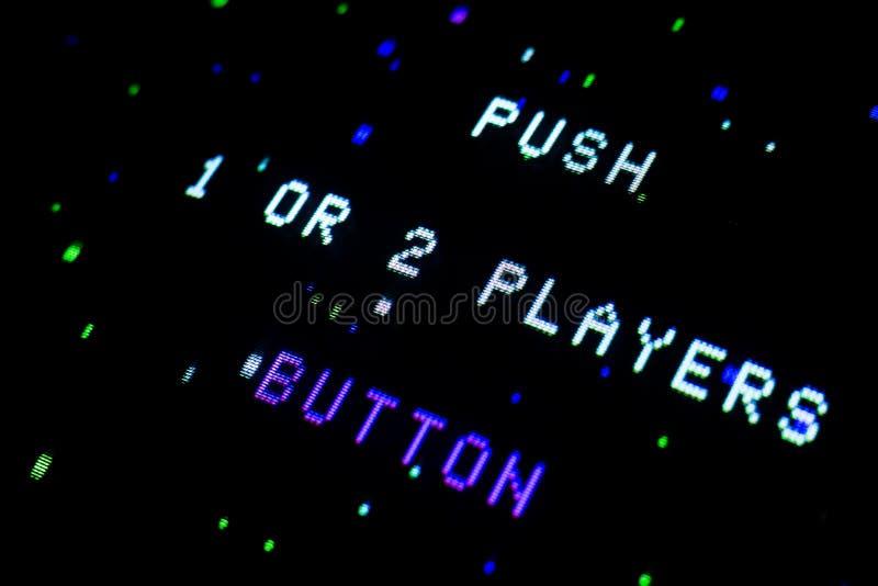 O detalhe em uma tela video da arcada velha com os jogadores do impulso 1 ou 2 do texto abotoa-se imagem de stock royalty free