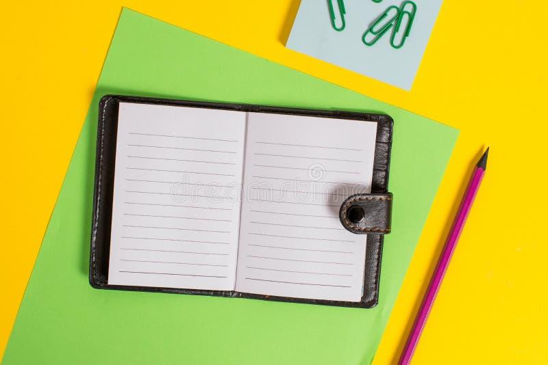 O diário fechado de couro escuro privado próximo da vista dianteira com o bloco de notas de papel listrado do marcador da folha g imagem de stock royalty free