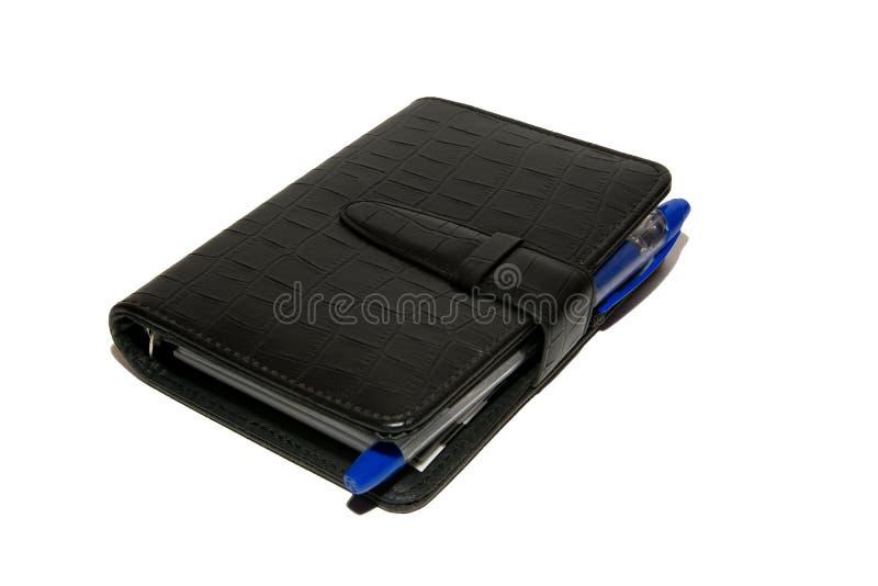 O diário preto com uma pena de esferográfica azul encontra-se em uma tabela branca Isolado foto de stock