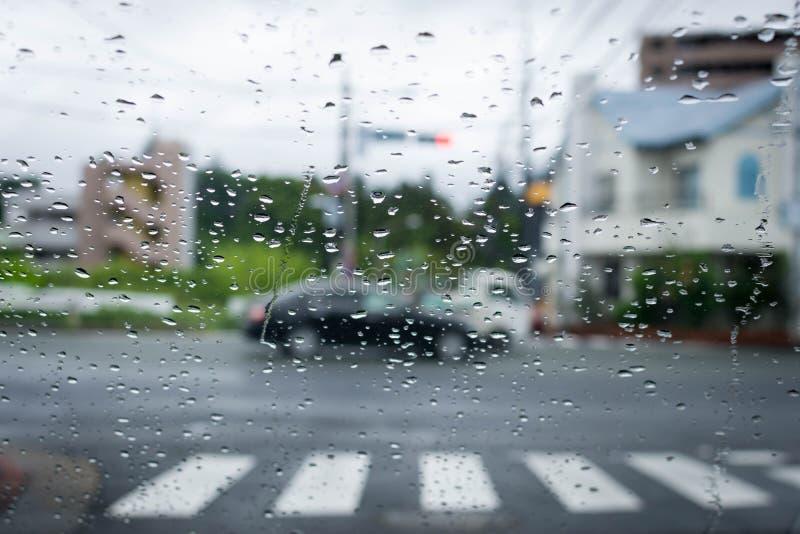 O dia chuvoso e sombrio na estrada com carros e tráfego e chuva é focalizado no para-brisa do carro fotografia de stock royalty free