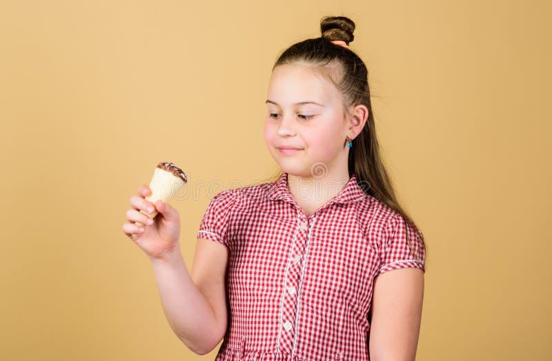 O dia das crian?as internacionais Conceito do guloso Crian?a pequena da menina para comer o fundo bege do cone de gelado O ver?o  fotos de stock