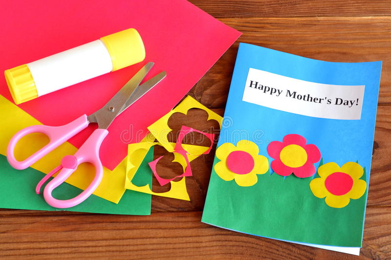 O dia de mãe feliz do cartão - ofícios das crianças Tesouras, colagem, sucatas de papel, folhas de papel no fundo de madeira marr imagem de stock
