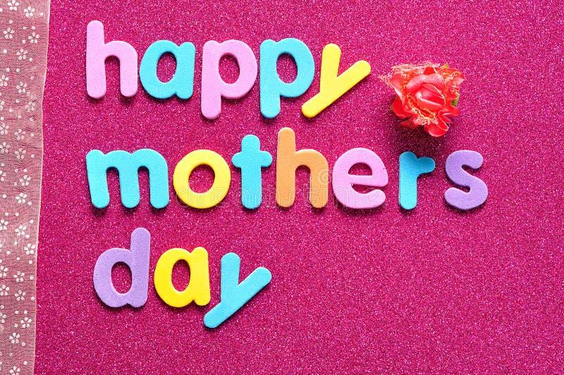 O dia de mães feliz em um fundo cor-de-rosa com uma fita cor-de-rosa e um artificial aumentou imagens de stock royalty free