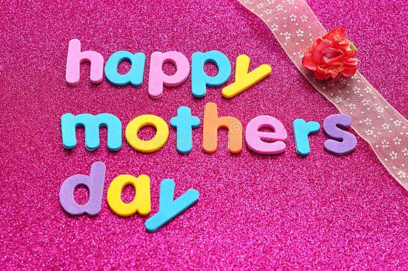 O dia de mães feliz em um fundo cor-de-rosa com uma fita cor-de-rosa e um artificial aumentou foto de stock