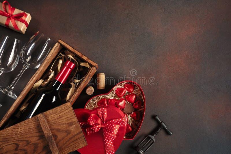 O dia de Valentim com corações, vinho, corkscrew, vidros, presentes, uma caixa coração-dada forma e um quadro-negro imagens de stock