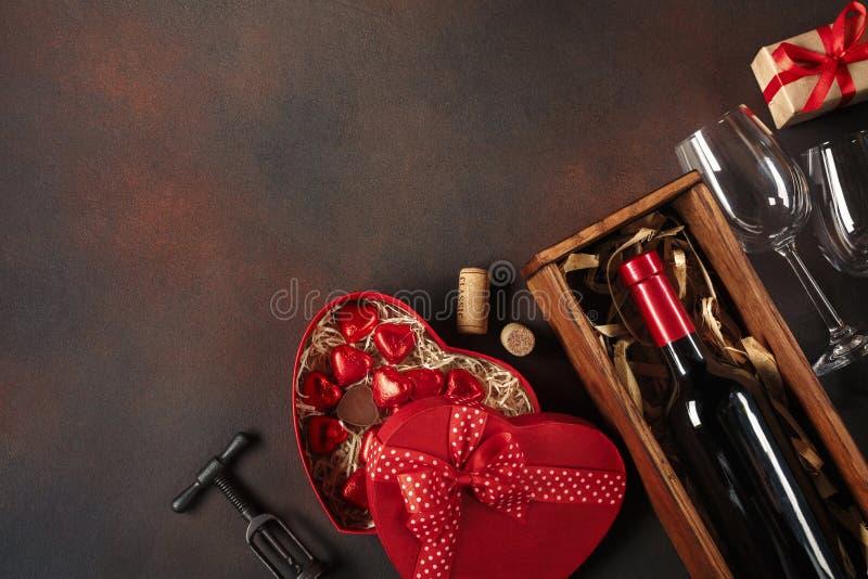 O dia de Valentim com corações, vinho, corkscrew, vidros, presentes, uma caixa coração-dada forma e um quadro-negro imagens de stock royalty free