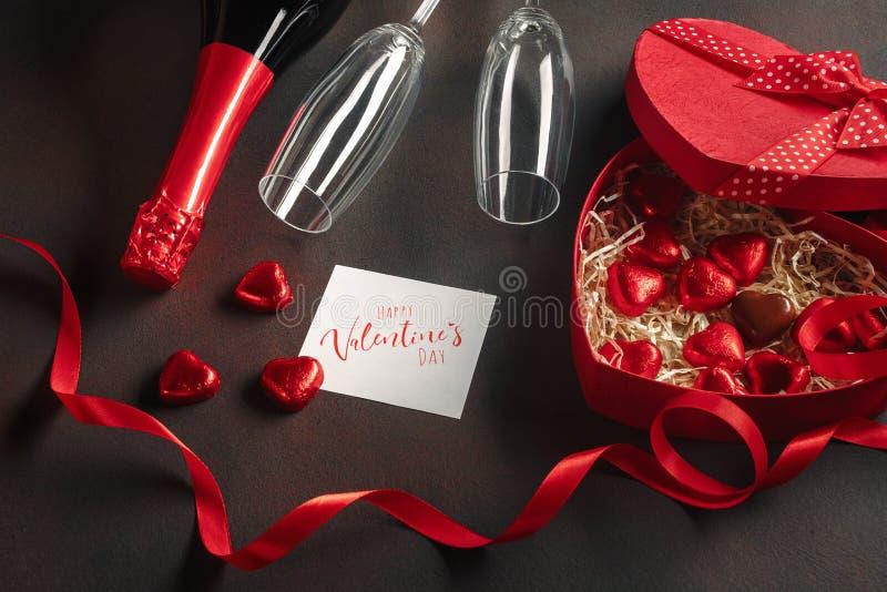 O dia de Valentim com uma caixa dos chocolates sob a forma de um coração com uma garrafa do champanhe com vidros e uma nota imagens de stock