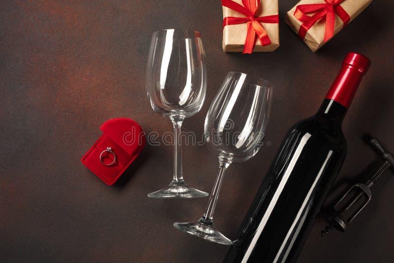 O dia de Valentim com uma garrafa do vinho e um vidro e um anel de noivado Vista superior com espaço da cópia fotos de stock