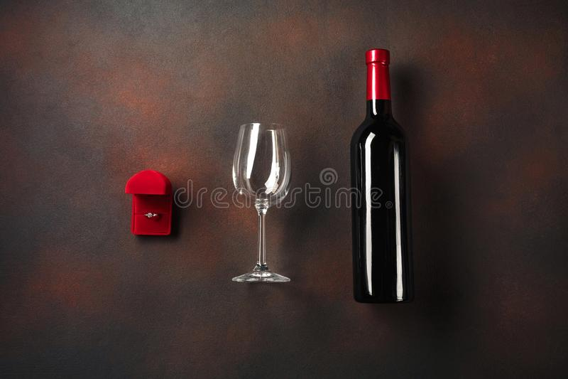 O dia de Valentim com uma garrafa do vinho e um vidro e um anel de noivado Vista superior com espaço da cópia fotografia de stock