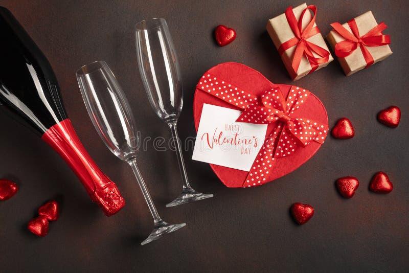 O dia de Valentim com uma garrafa de vidros do champanhe dos chocolates e dos presentes Vista superior com espaço da cópia imagem de stock