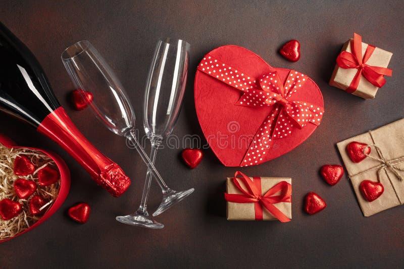 O dia de Valentim com uma garrafa de vidros do champanhe dos chocolates e dos presentes Vista superior com espaço da cópia imagem de stock royalty free