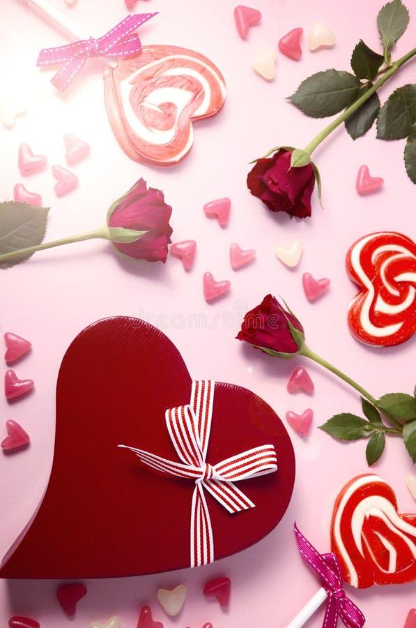 O dia de Valentim em cima com rosas, pirulitos e presente e alargamento da lente foto de stock royalty free