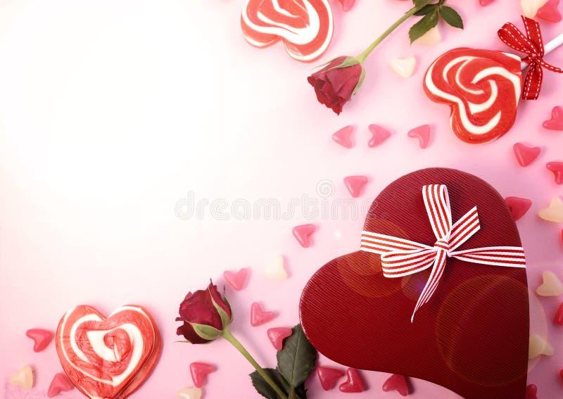 O dia de Valentim em cima com rosas, pirulitos e presente e alargamento da lente imagens de stock royalty free