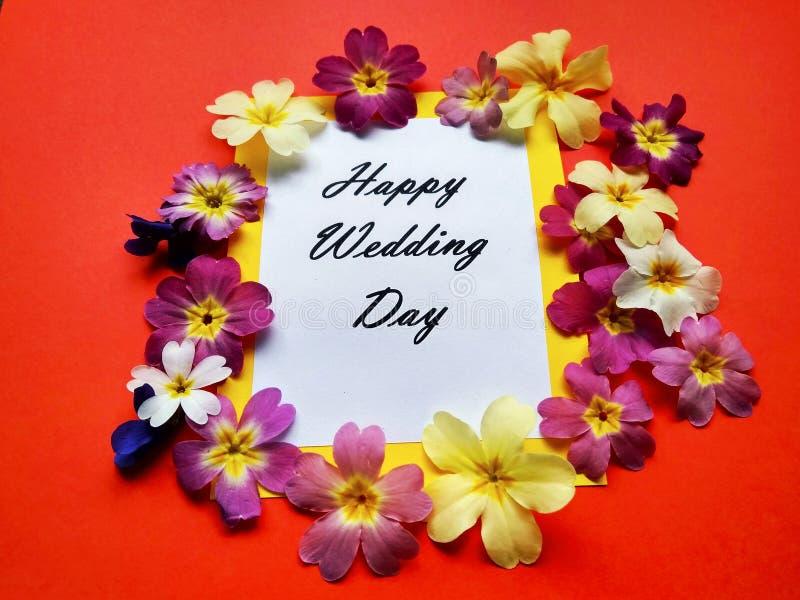 O dia do casamento feliz da inscrição com flores em um fundo colorido fotos de stock