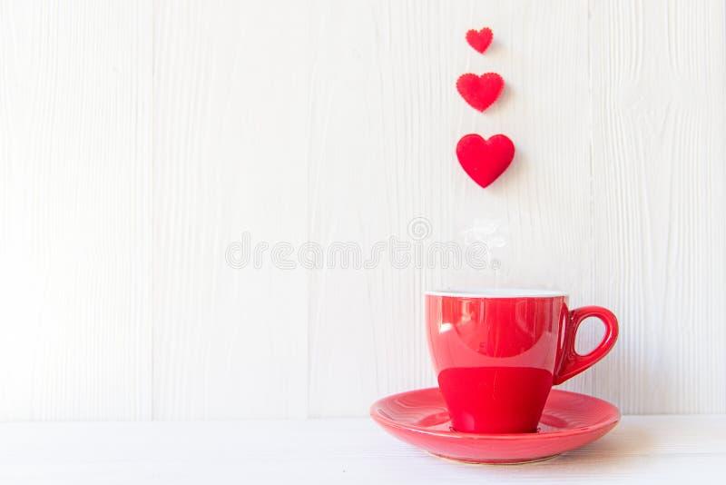 O dia do ` s do Valentim com café vermelho do copo costurou a beira da fileira dos corações do descanso, fundo branco de madeira foto de stock royalty free