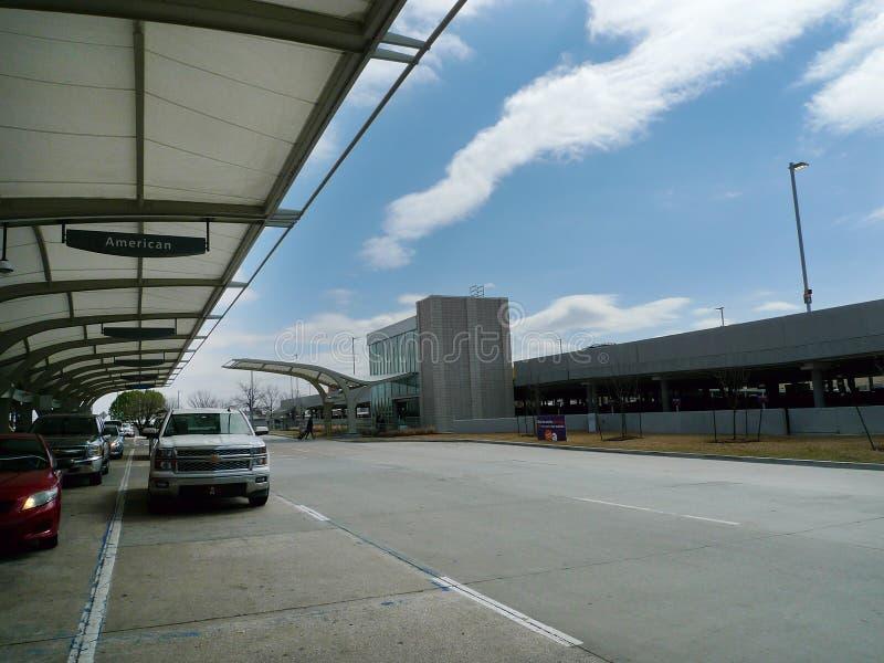 O dia exterior do aeroporto internacional de Tulsa, veículos deixa cair dentro fora a pista imagens de stock