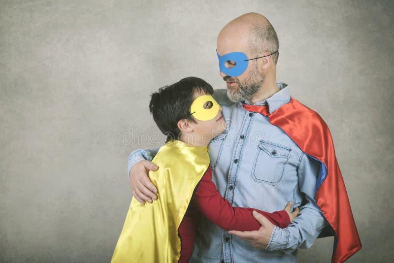 O dia, o pai e o filho de pai vestidos como um super-herói fotografia de stock